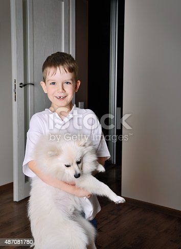 istock smilinng little boy 6-7 years old holding the dog indoor 487081780