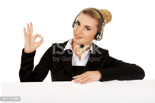 istock Smille call center woman holding empty banner and showing OK 614151684