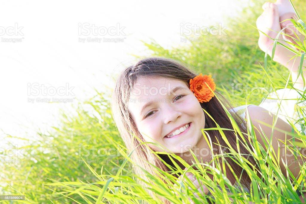 smilling girl lying in green grass stock photo