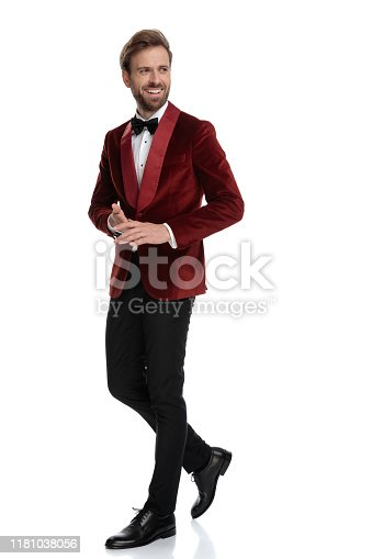smiling groom wearing red velvet tuxedo, walking and looking to side, smiling, isolated on white background in studio