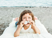 Smilling lovely child girl on the beach with sea view.Vacation,summer concept