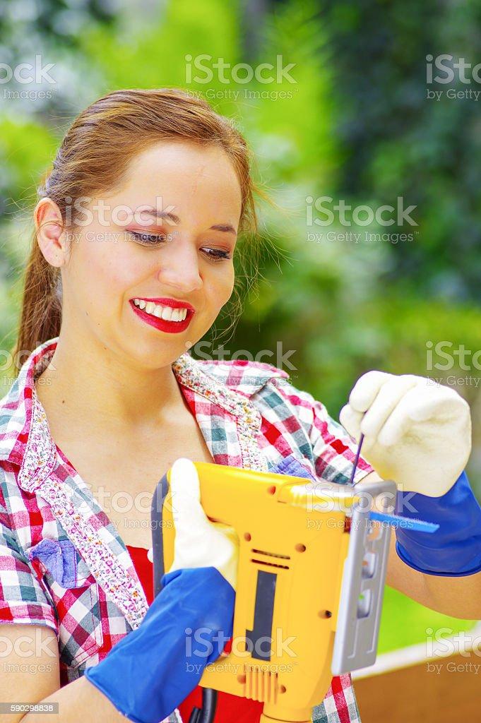 smilling woman adjust the blade to the jigsaw Стоковые фото Стоковая фотография
