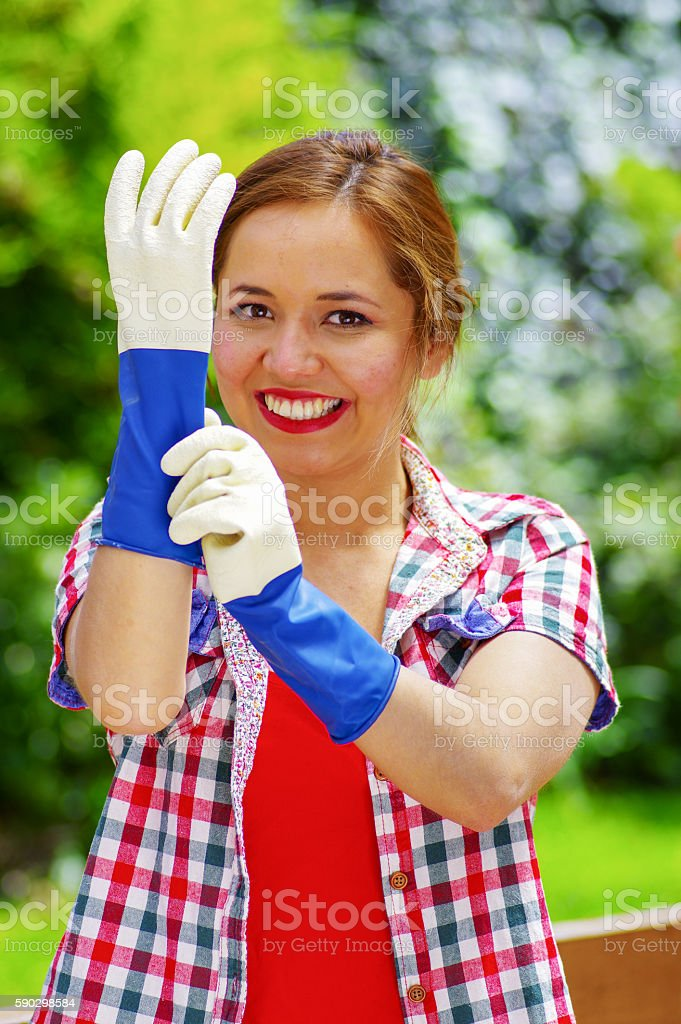 smilling women with colofull clothes putting on work gloves royaltyfri bildbanksbilder