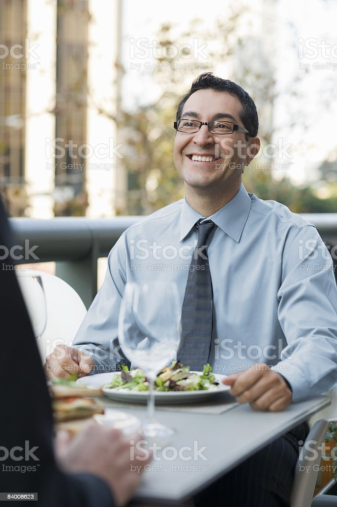 Smilng man in cafe with salad. royalty free stockfoto