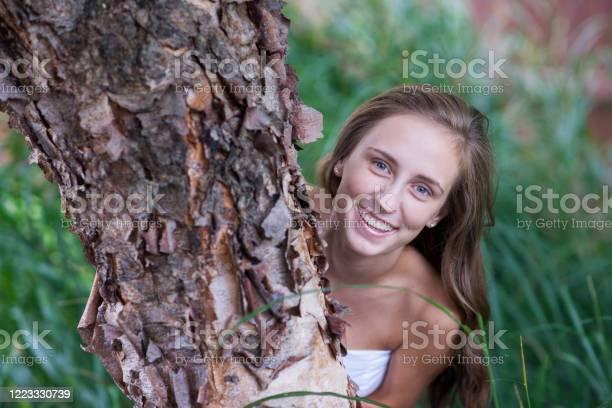 Photo of Smilng teen hugs a river birch tree