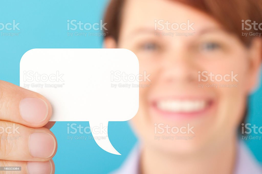Smilng woman holding blank white speech bubble royalty-free stock photo