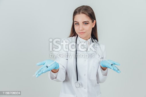 140378701istockphoto Smilng young female doctor showing to the camera open palms with syringes. 1156708324