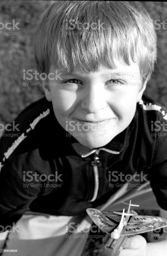 Smirking child with a toy airplane royalty-free stock photo