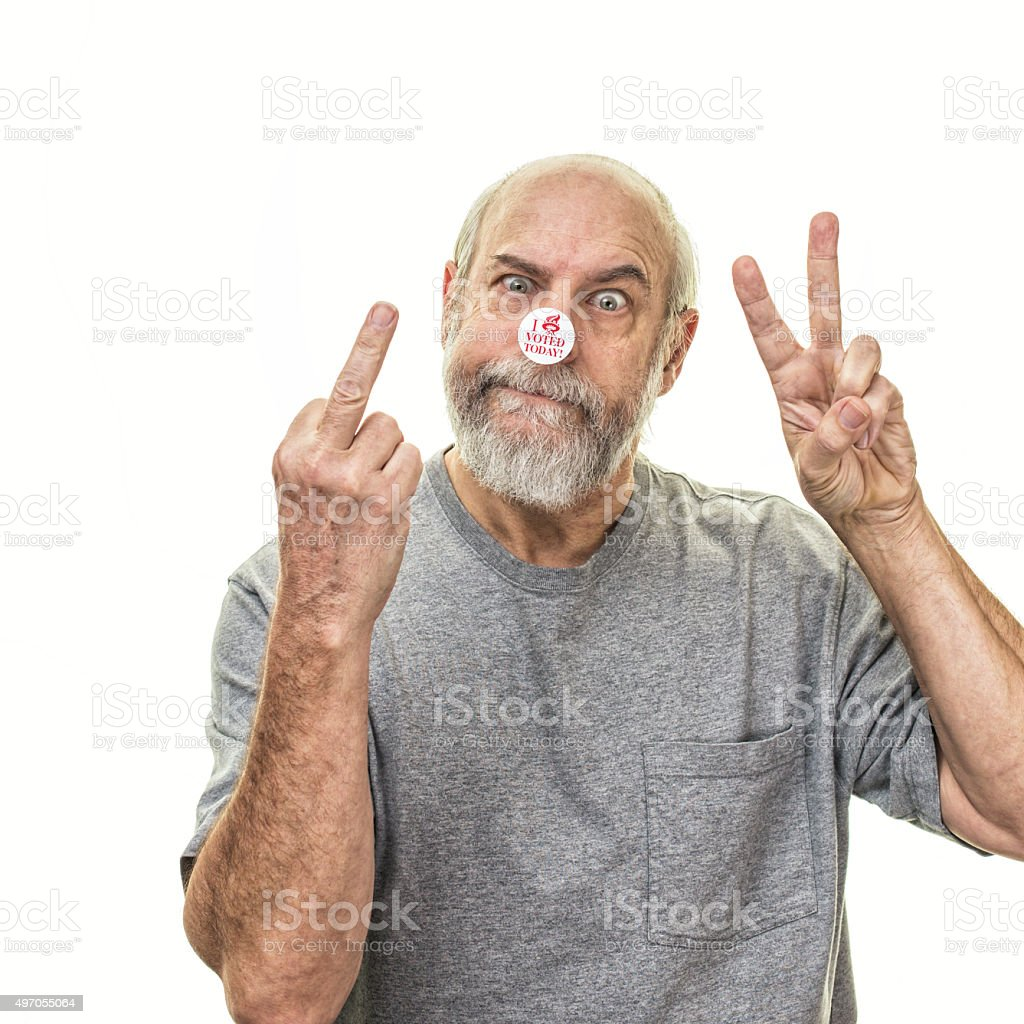 Smirking Senior Voter Flipping Middle Finger And Victory Hand Gestures stock photo
