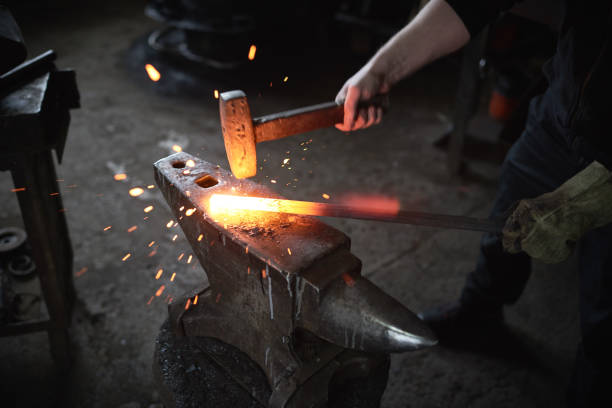 Smithing process Blacksmith hitting red-hot metal with hammer to change shape anvil stock pictures, royalty-free photos & images