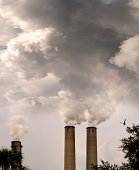 Environmental image of two factory chimneys and smokes in the air