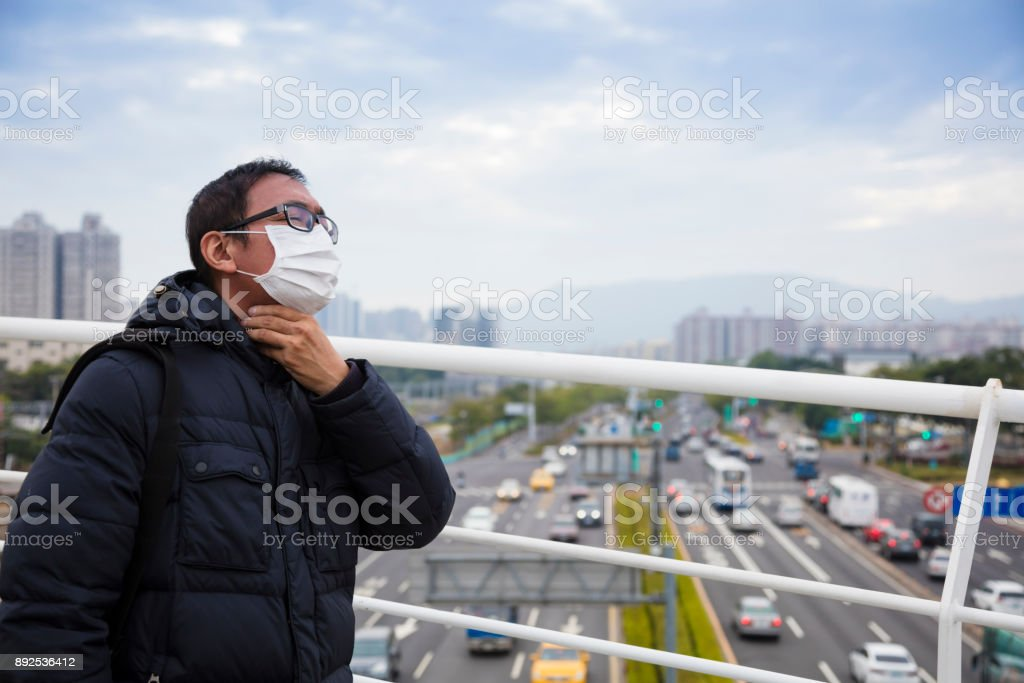 Smog in the city.men in medical mask with sore throat stock photo