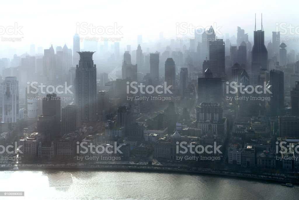 Smog lies over the skyline of Historical architecture and modern skyscraper on the bund of Shanghai city in misty sunrise, Shanghai, China vintage picture style stock photo