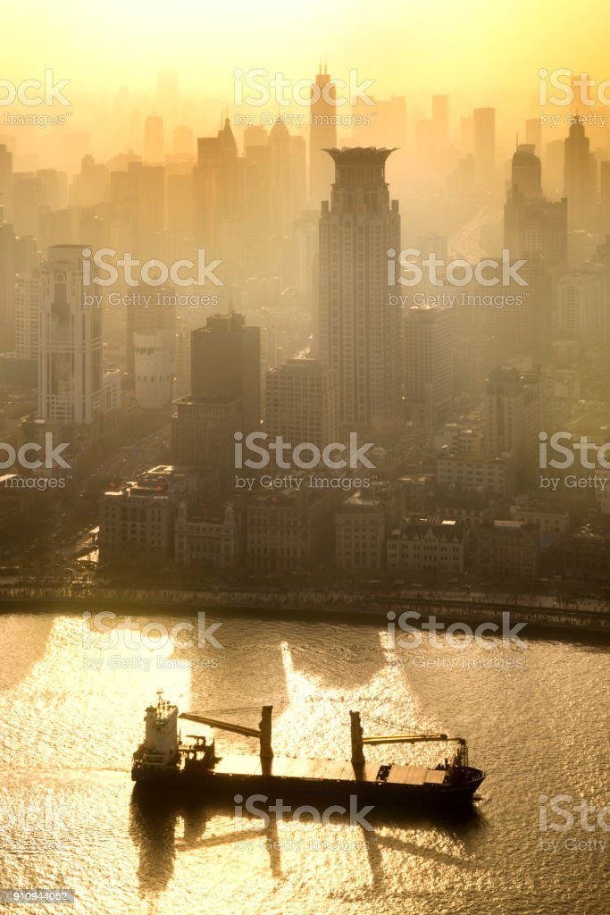Smog lies over the skyline of Historical architecture and modern skyscraper on the bund of Shanghai city in misty gold lighting sunrise, Shanghai, China vintage picture style stock photo
