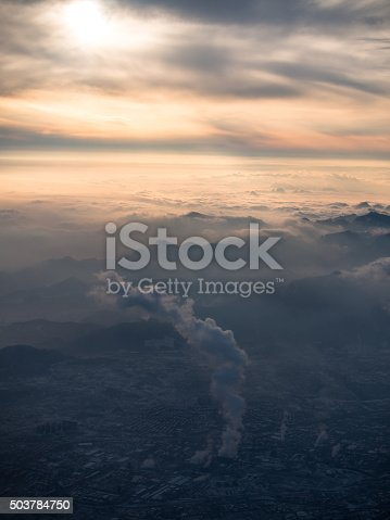 Toned image of smog over Beijing plant with a large column of toxic smoke in the background of a sunset with mountains and cumulus clouds
