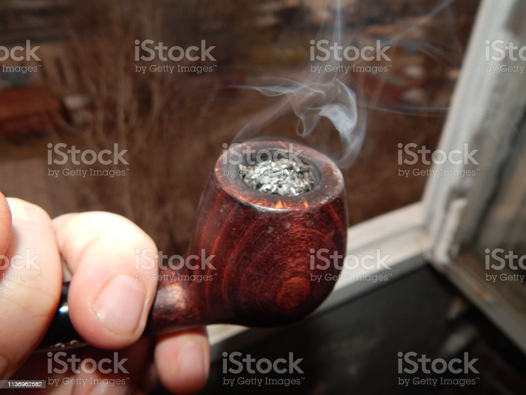 I smoke a pipe on the balcony of the house with real tobacco stock photo
