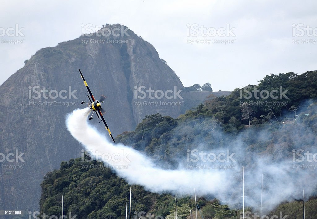 Smoke Airplane in motion with mountain at background royalty-free stock photo