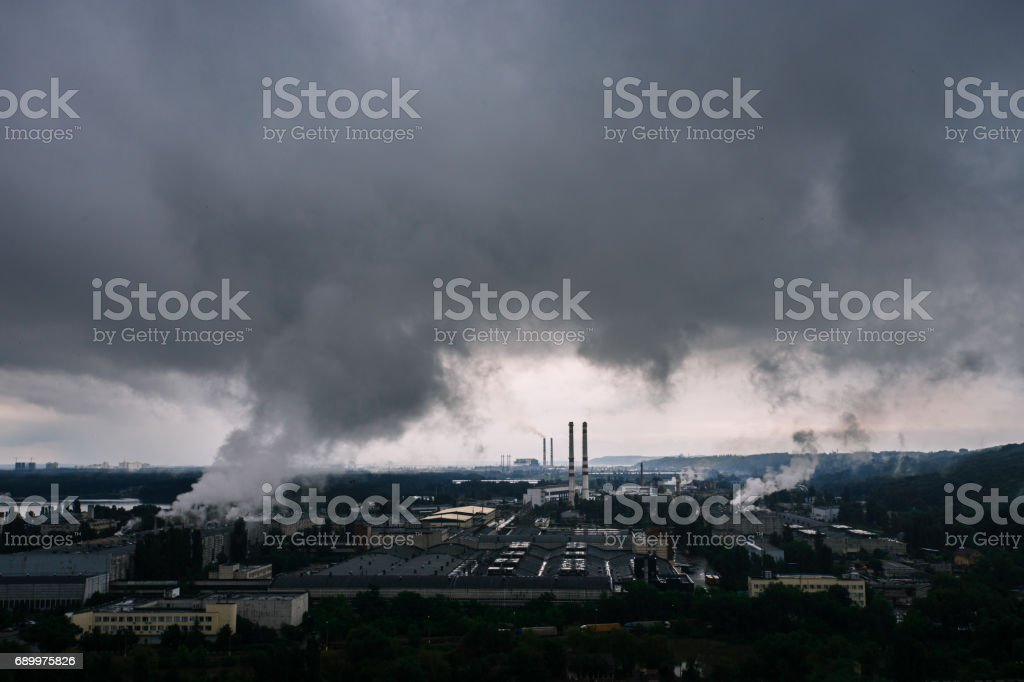 Humo y el cielo dramático después de la tormenta por encima de la zona industrial cerca de la ciudad - foto de stock