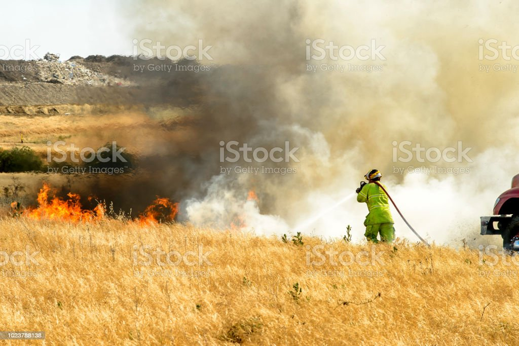 Smoke and Flames From Grass Wildfire With Unrecognizable Firefighter stock photo