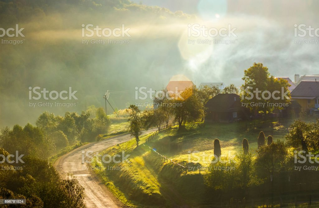 smoke and fog over the village at sunrise stock photo