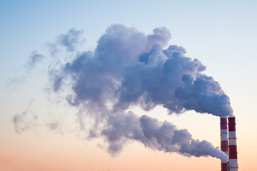 Smoke, fumes coming out of pipes of factory producing heat for central heating in winter on the background of skies.