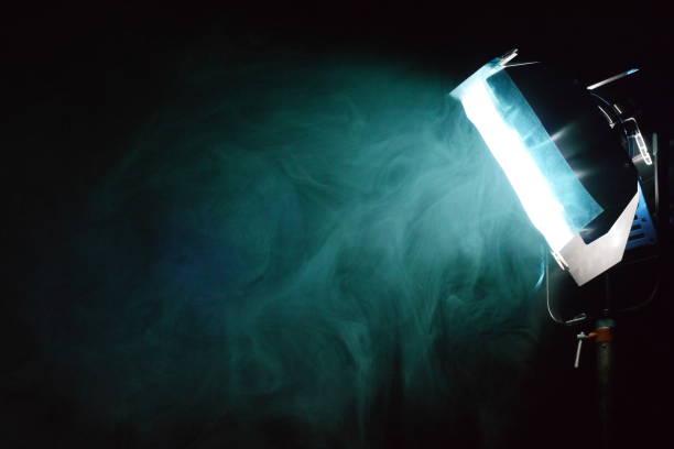 smoke around a filtered light on a film set stock photo