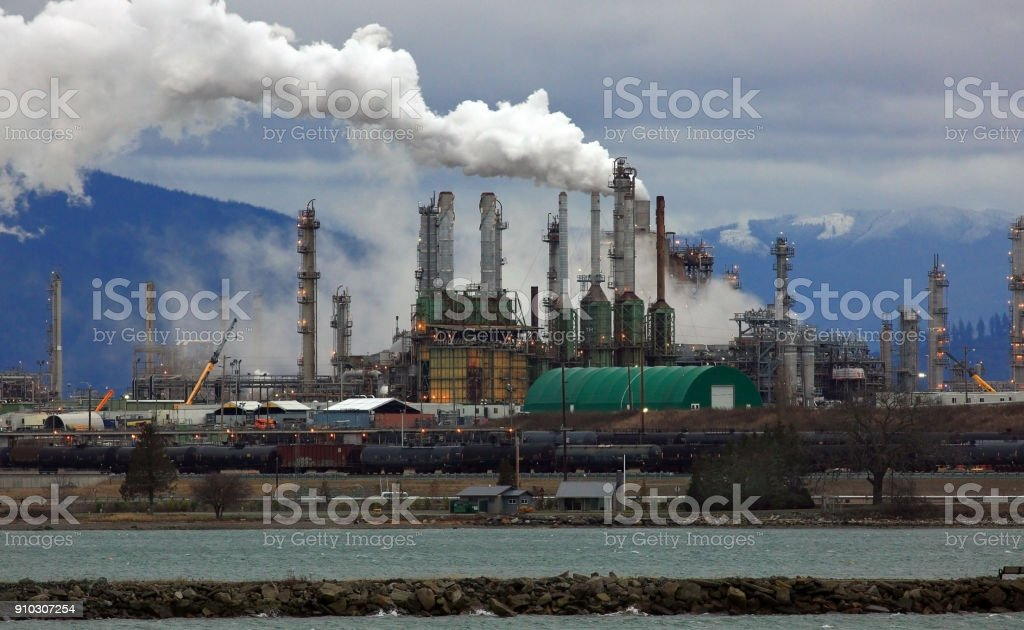 Smoke Billows from Oil Refinery Chimneys stock photo