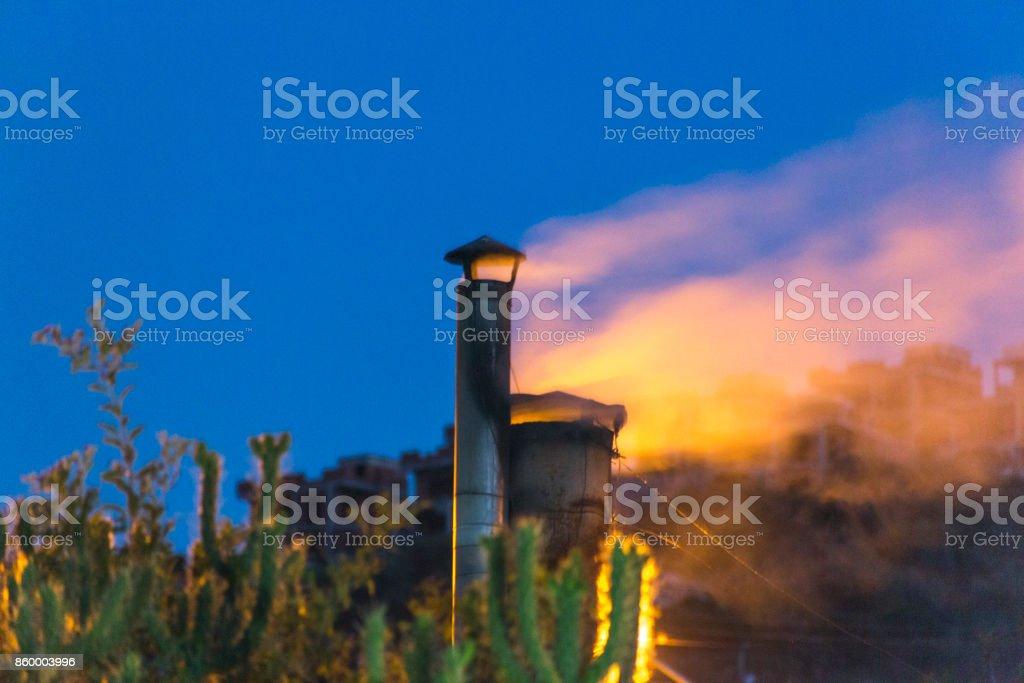 smoke coming out of kitchen chimney at night in gulluk bodrum turkey stock photo