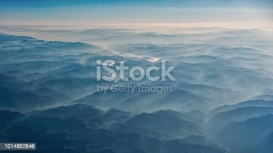 Smoke covering mountains seen from an airplane.