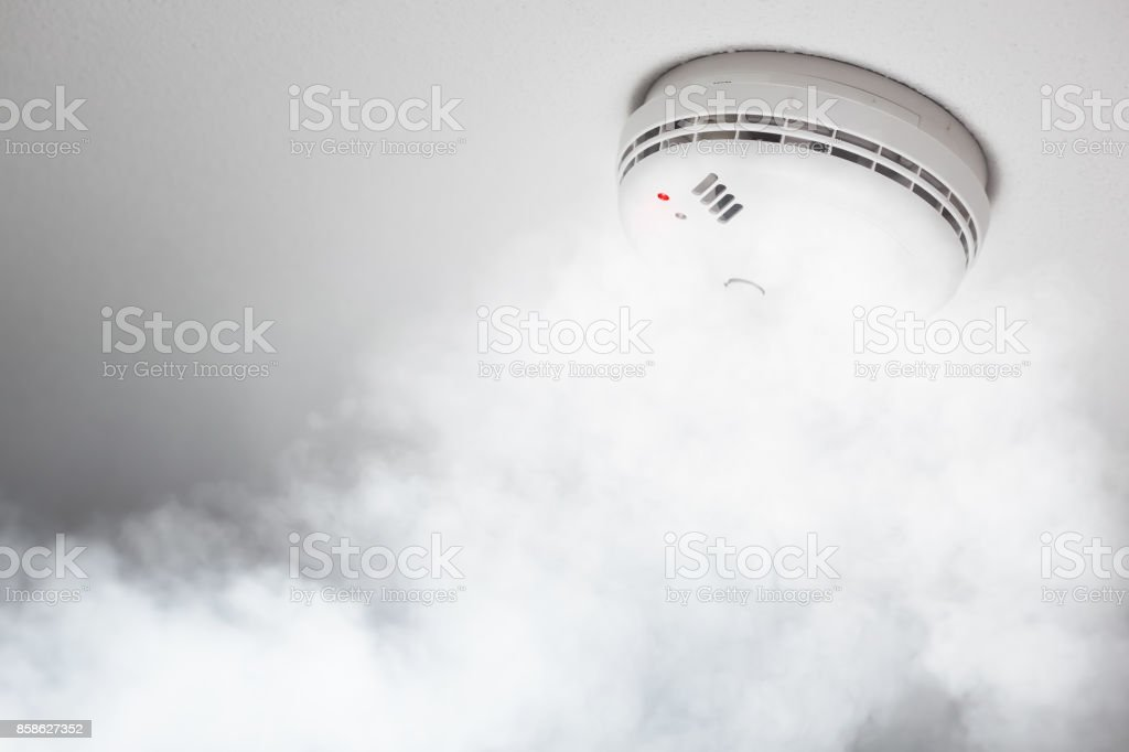 smoke detector of fire alarm in action, white background stock photo