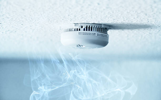 Smoke detector A smoke detector installed at a ceiling with smoke. Small depth of field. sensor stock pictures, royalty-free photos & images