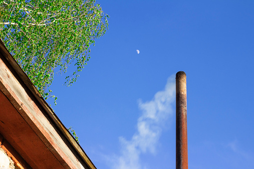smoke from a steel pipe against a blue sky with the moon