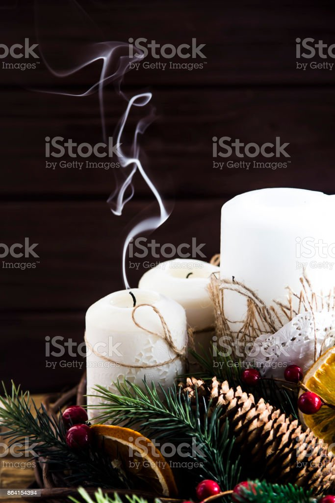 smoke from an extinguished white candle - a decorative Christmas arrangement with a wreath and tree branches. Hygge concept royalty-free stock photo