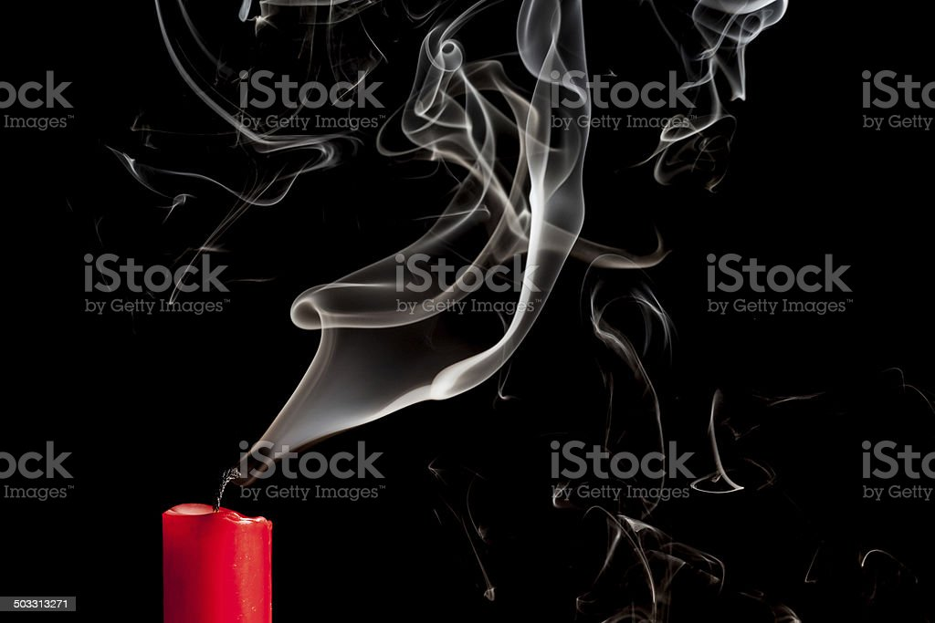 Smoke from blown out red candle stock photo