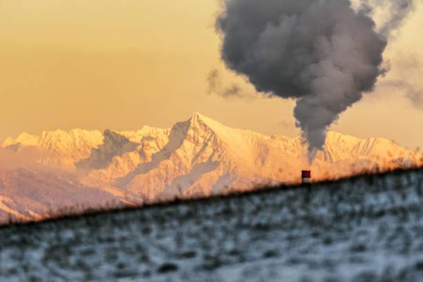 Smoke from chimney and hill at background. Snowy peak Krivan, Slovakia stock photo