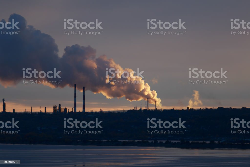 smoke from factory chimneys illuminated by the setting sun stock photo