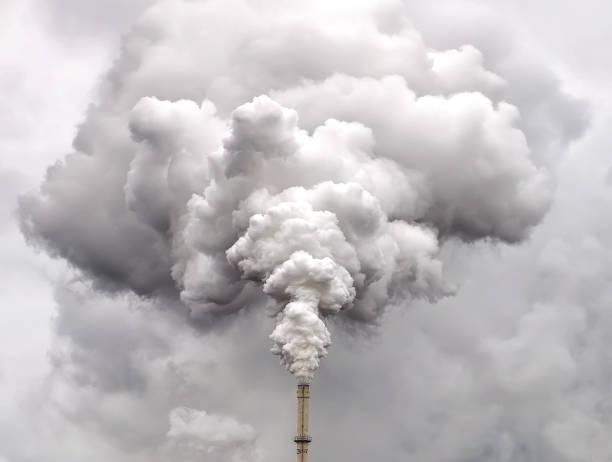 humo de la pipa de la fábrica contra el oscuro cielo cubierto - contaminación ambiental fotografías e imágenes de stock