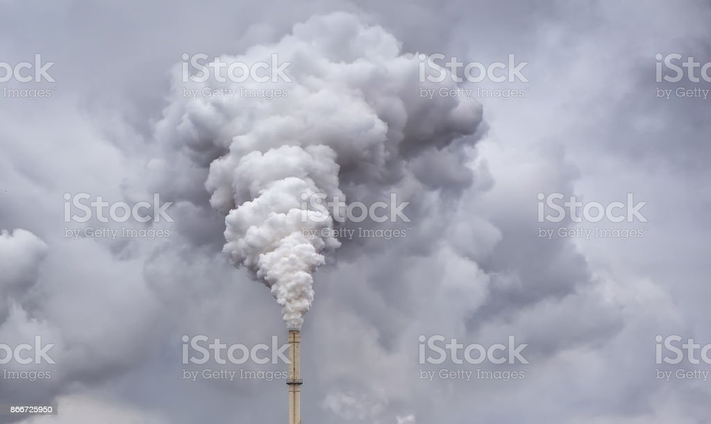 Smoke from factory pipe against dark overcast sky stock photo