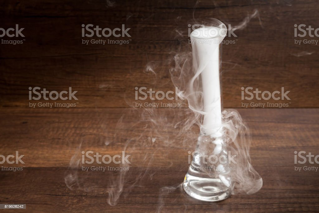 Smoke from putting dry ice in the water, in transparent vest, on wooden background, dark and mysterious style stock photo