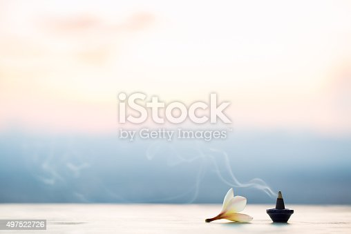 istock Smoke incense cones with plumeria flower on sunset 497522726