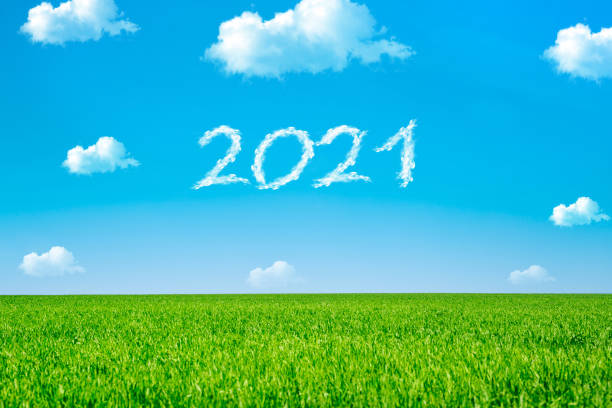 Smoke inscription of the year 2021 on blue sky. New Year celebration concept. stock photo