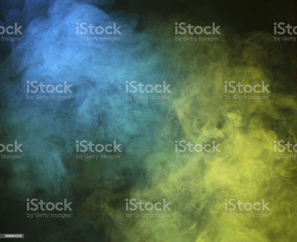 Smoke lit up with blue and yellow lights stock photo