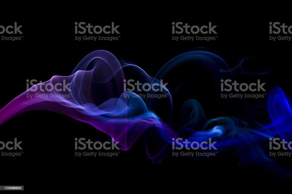 Smoke moving through the air with a hint of blue and purple  stock photo