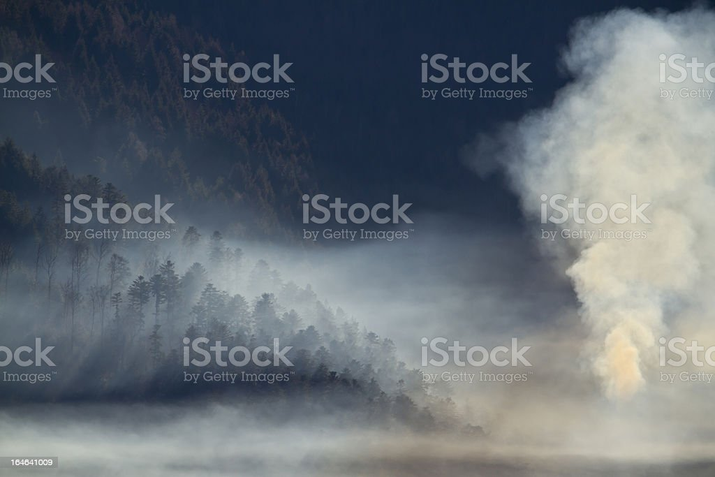 Smoke of a fir tree forest fire in mountain forests royalty-free stock photo