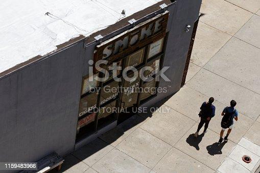 Philadelphia, PA, USA - July 1, 2019: Two people walk past a smoke shop in the Manayunk neighborhood of Philadelphia, Pennsylvania.