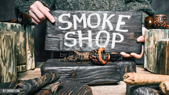 Tobacco and pipes on wood counter. Human hands holding wooden signboard with text 'Smoke shop'. Close-up view