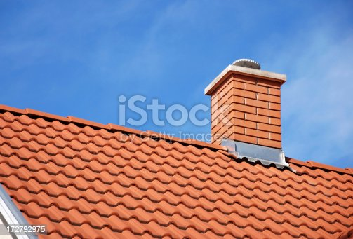 smoke stack on the tiled roof of a family house
