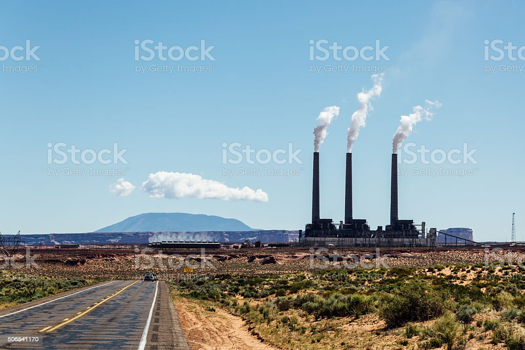 Smoke stacks from industrial plant against sky stock photo