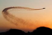 Plane leaving dark smoke trail over sky