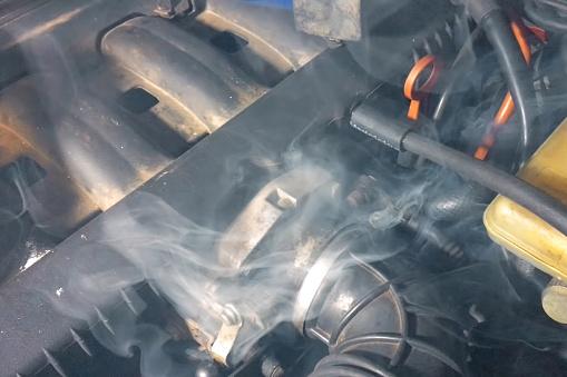 Smoke under the hood of a car. Car engine smokes.